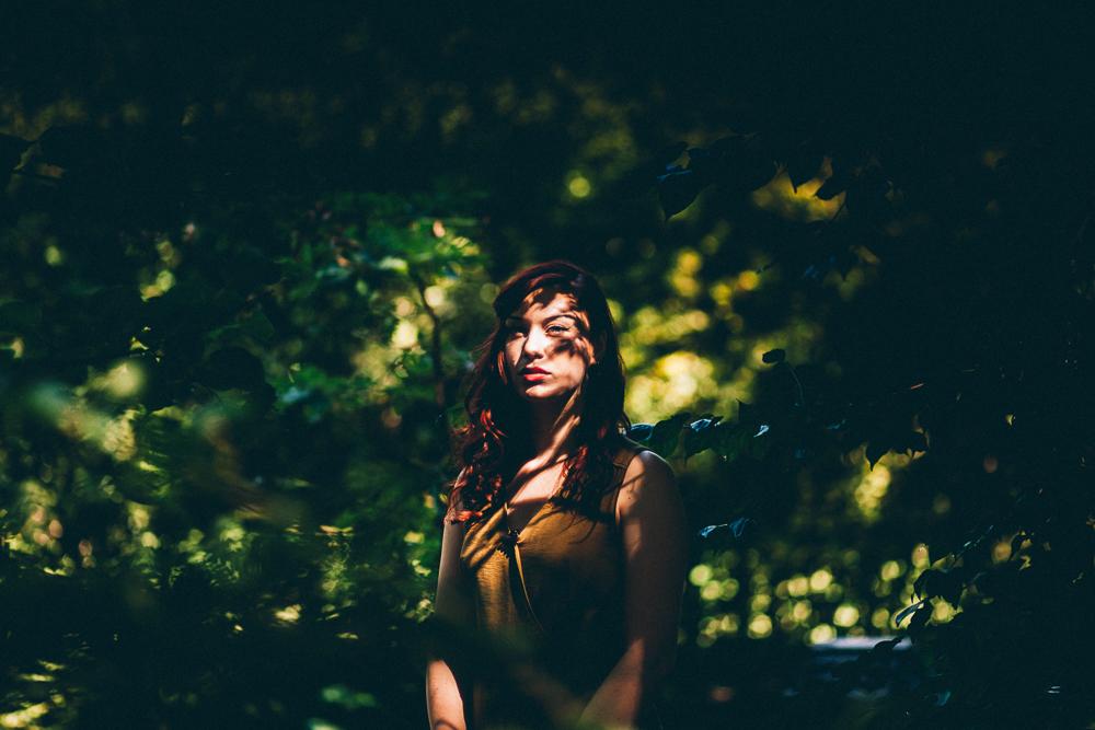 shooting femme posant aux milieu des feuilles qui ombrent son visage